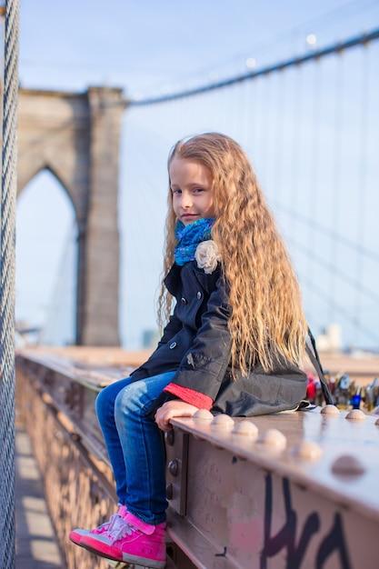 Bambina adorabile che si siede al ponte di brooklyn con la vista sulla strada Foto Premium