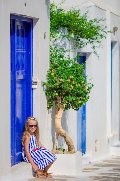 Bambina adorabile che si siede davanti alla porta blu all'aperto al villaggio tradizionale greco tipico su mykonos in grecia Foto Premium