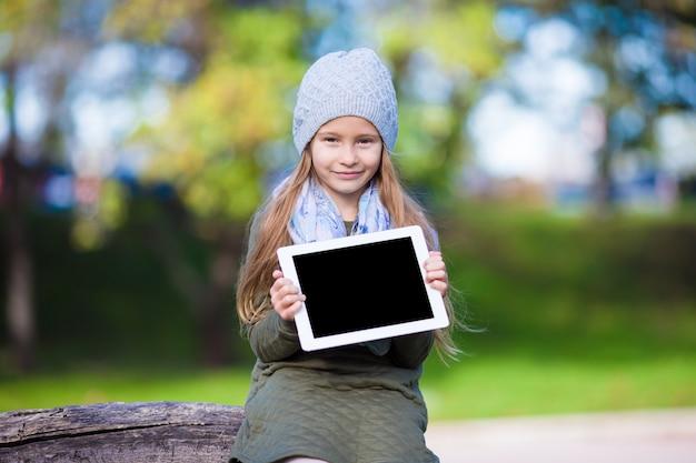 Bambina adorabile con il pc della compressa all'aperto nel giorno soleggiato di autunno Foto Premium
