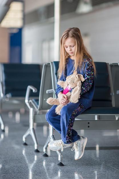 Bambina adorabile in aeroporto vicino alla grande finestra dell'interno Foto Premium