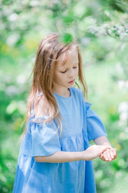 Bambina adorabile nel giardino delle mele di fioritura il bello giorno di molla Foto Premium