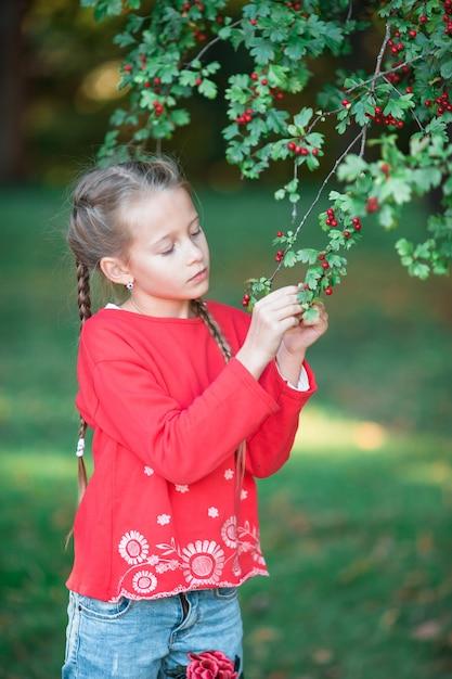 Bambina adorabile nel giardino di fioritura di melo il giorno di molla Foto Premium
