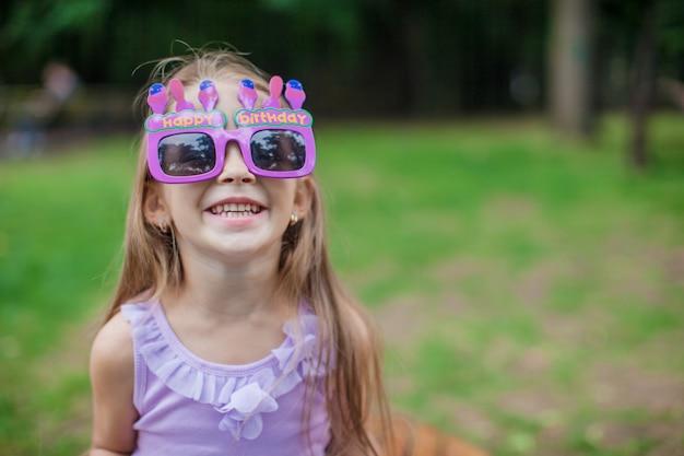 Bambina adorabile nel sorridere di vetro di buon compleanno all'aperto Foto Premium