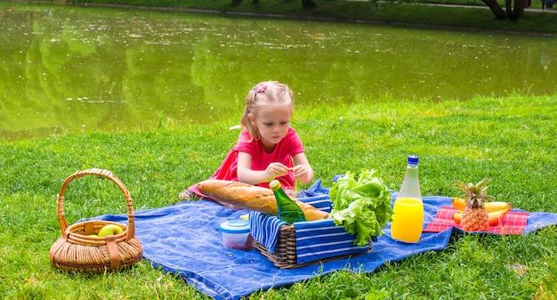 Bambina adorabile sul picnic all'aperto vicino al lago Foto Premium