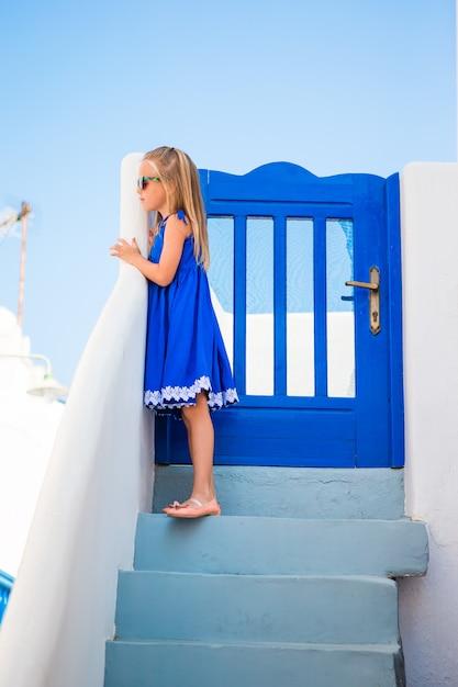 Bambina alla via del tipico villaggio greco con pareti bianche e passaggi in grecia Foto Premium
