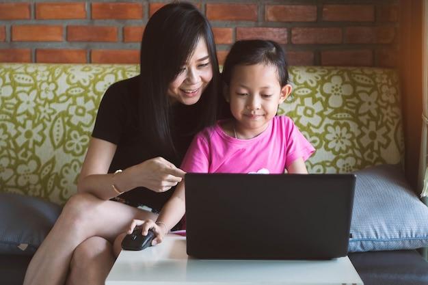 Bambina asiatica che gioca al computer portatile con sua madre a casa. Foto Premium