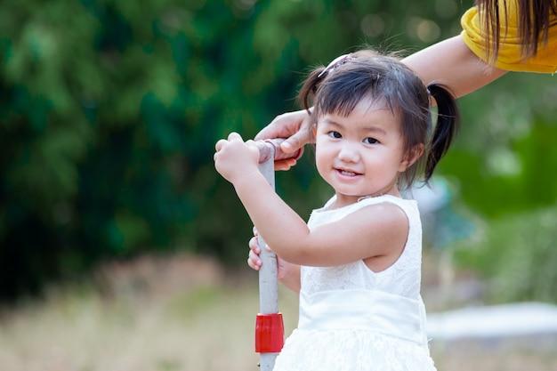Bambina asiatica sveglia che sorride e che gioca nel parco con divertimento e felicità Foto Premium