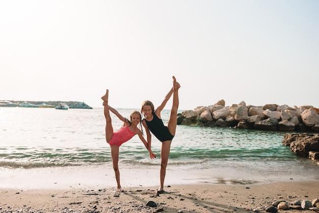 Bambina attiva in spiaggia divertendosi molto. ragazzo carino fare esercizi sportivi in riva al mare Foto Premium