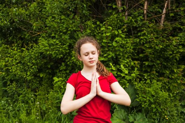 Bambina attraente che prega con gli occhi chiusi in natura Foto Gratuite