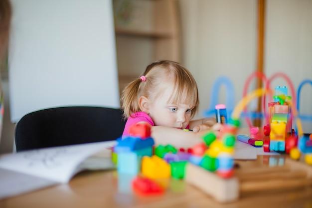 Bambina bella seduta alla scrivania scrivania Foto Gratuite
