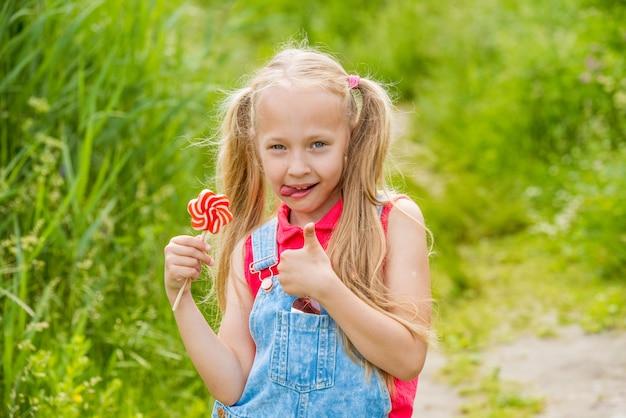 Bambina bionda con capelli lunghi e caramelle su un bastone Foto Premium