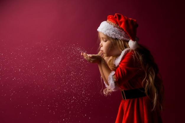 Bambina bionda in un vestito di babbo natale soffia neve dalle sue mani Foto Premium