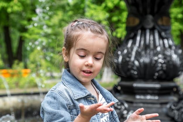 Bambina carina bagna le mani nella fontana Foto Gratuite