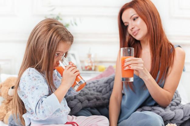 Bambina carina godendo, giocando e creando con il succo con la madre Foto Gratuite