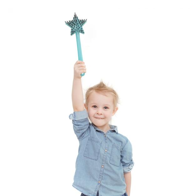 Bambina caucasica con capelli biondi in una camicia di jeans che tiene una spazzola Foto Premium
