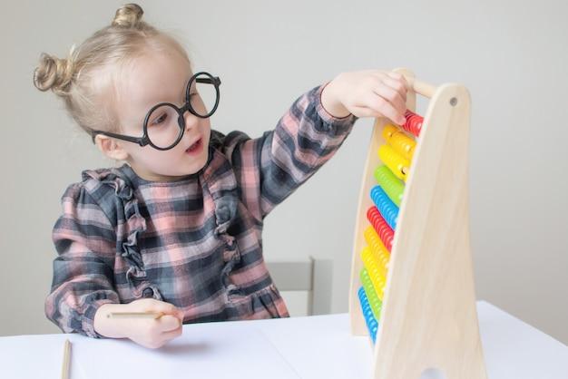 Bambina caucasica con gli occhiali rotondi. piccola maestra. umorismo divertente con gli occhiali. stile retrò Foto Premium