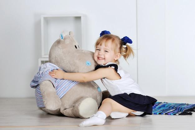 Bambina che abbraccia un ippopotamo dell'orsacchiotto Foto Premium