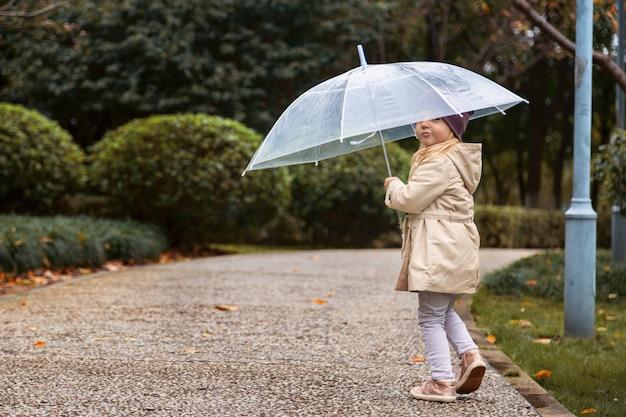 Bambina che cammina in un parco sotto un ombrello durante una pioggia Foto Premium