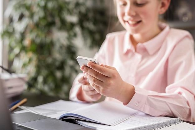 Bambina che controlla il suo telefono nella classe a casa Foto Gratuite