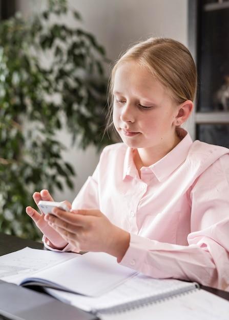 Bambina che controlla il suo telefono nella classe online Foto Gratuite