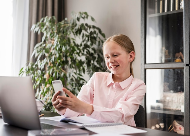 Bambina che controlla il suo telefono nella classe Foto Gratuite