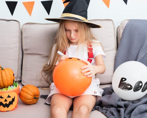 Bambina che disegna un baloon di halloween Foto Gratuite