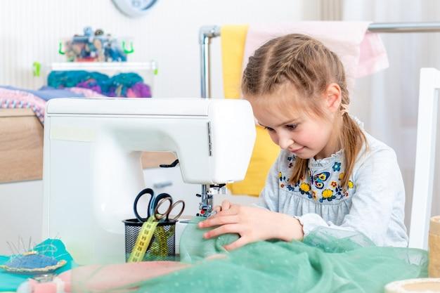 Bambina che fa i mestieri alla macchina per cucire Foto Premium