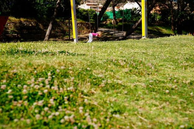 Bambina che gioca con un'oscillazione in un prato durante il fine settimana estivo. Foto Premium