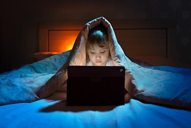 Bambina che gioca tablet sotto coperta durante la notte Foto Premium
