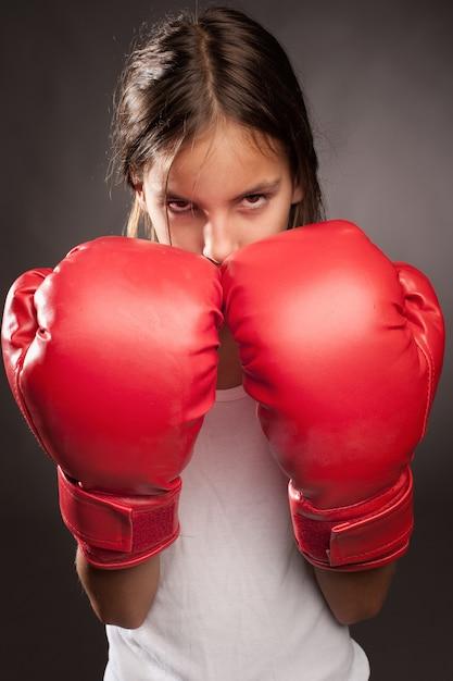 Bambina che indossa guantoni da boxe rossi Foto Premium