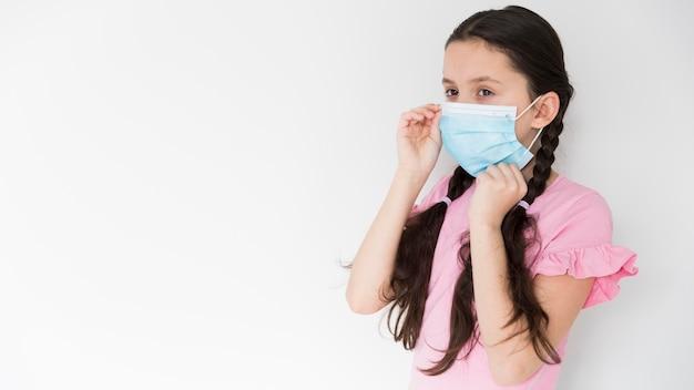Bambina che indossa una maschera medica Foto Gratuite