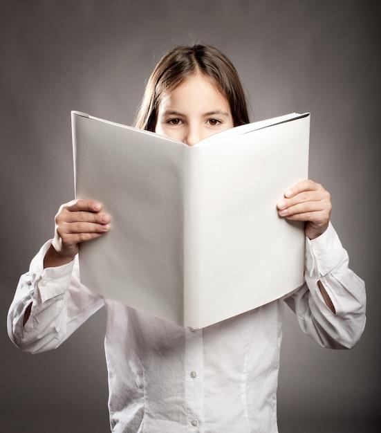 Bambina che legge un libro con copertina vuota Foto Premium