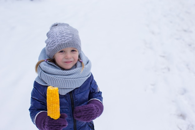 Bambina che mangia cereale all'aperto il giorno di inverno Foto Premium