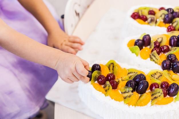 Bambina che mangia dolce con le sue mani. Foto Premium