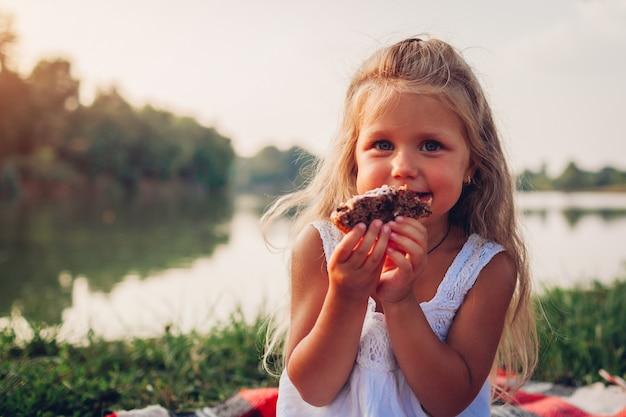 Bambina che mangia dolce sul picnic della famiglia dal fiume di estate, torta della tenuta del bambino Foto Premium