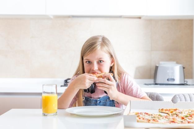 Bambina che mangia pizza che si siede al tavolo Foto Premium