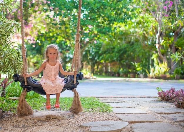 Bambina che oscilla su un'oscillazione nel cortile fiorito adorabile accogliente Foto Premium