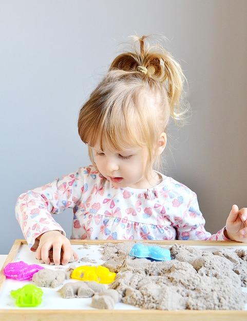 Bambina che paga con la sabbia cinetica a casa Foto Premium