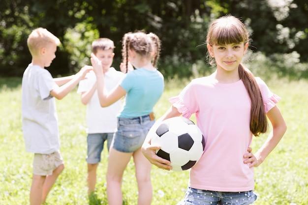 Bambina che posa con la palla di calcio Foto Gratuite