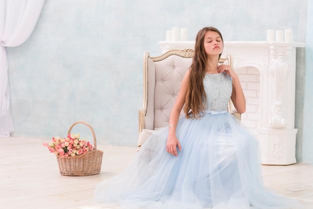 Bambina che posa mentre sedendosi sulla sedia del bracciolo vicino al canestro del fiore Foto Gratuite