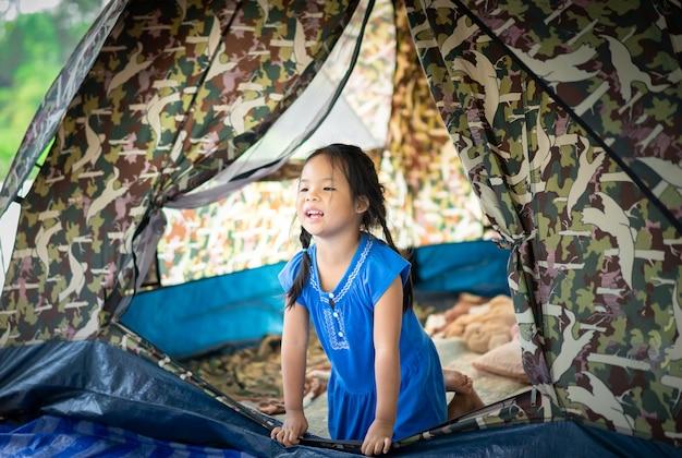 Bambina che si siede in tenda mentre andando in campeggio Foto Premium