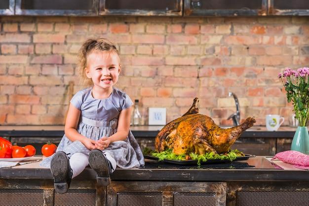 Bambina che si siede sul tavolo con tacchino arrosto Foto Gratuite
