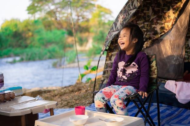 Bambina che si siede sulla sedia mentre andando in campeggio. Foto Premium