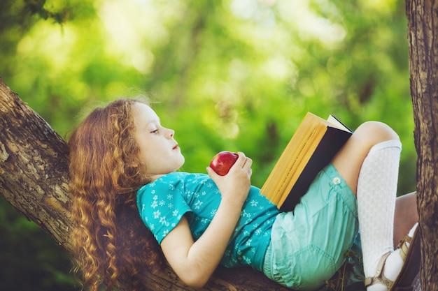 Bambina che si trova sul grande albero e legge il libro. Foto Premium