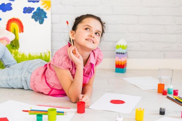 Bambina che si trova sul pavimento che osserva in su mentre verniciando sulla carta Foto Gratuite