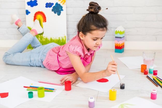 Bambina che si trova sulla pittura del pavimento con colore di acqua con il pennello su carta Foto Gratuite