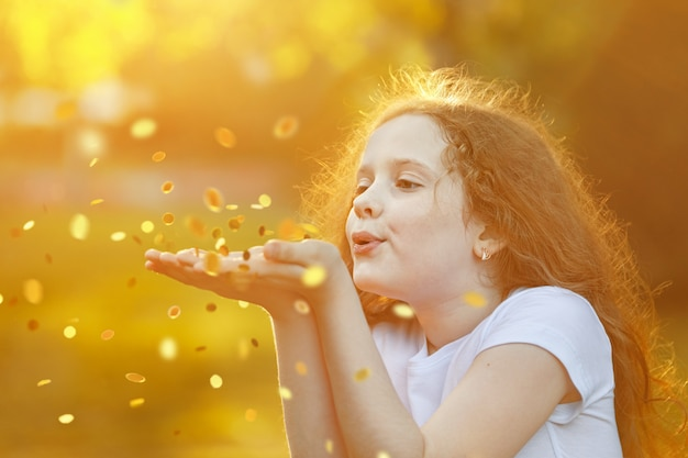 Bambina che soffia coriandoli d'oro con la sua mano. Foto Premium