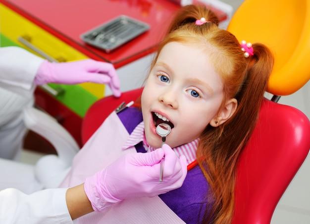 Bambina che sorride nella sedia dentale rossa. il dentista esamina i denti del paziente del bambino. Foto Premium