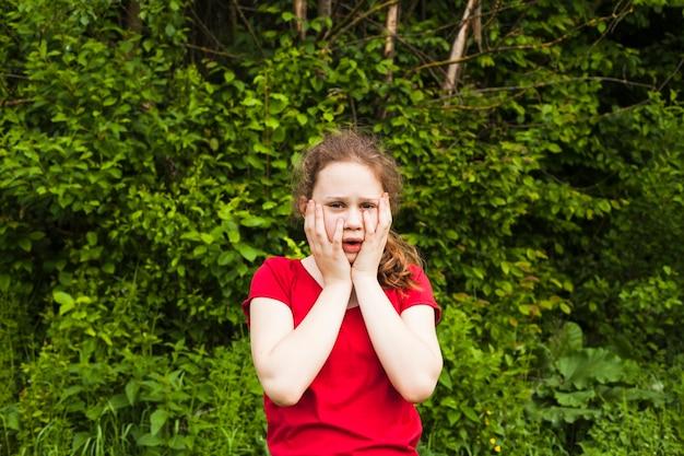 Bambina che sta nel parco che esamina macchina fotografica con l'espressione impaurita Foto Gratuite