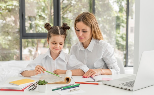 Bambina che studia a casa con il suo insegnante Foto Gratuite